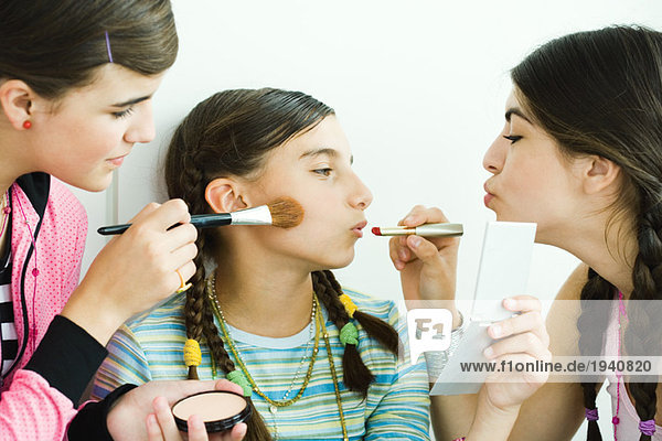 Two young female friends putting make-up on younger girl mouth