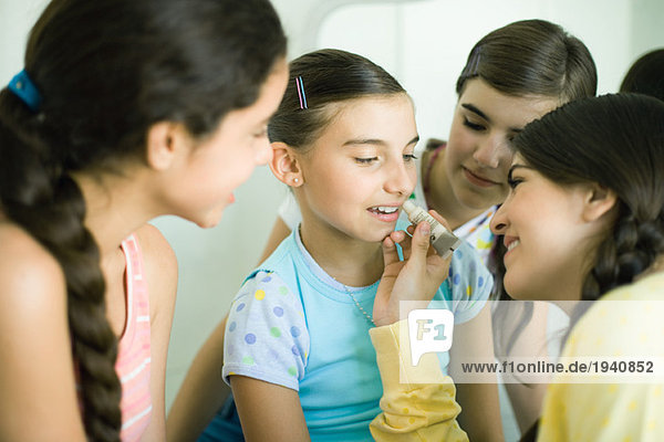 Young female friends putting make-up on younger girl