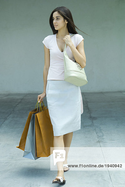 Woman carrying shopping bags  full length portrait
