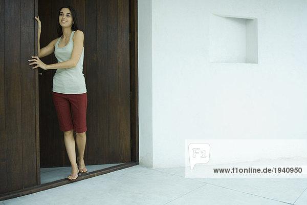 Woman standing in doorway  full length portrait