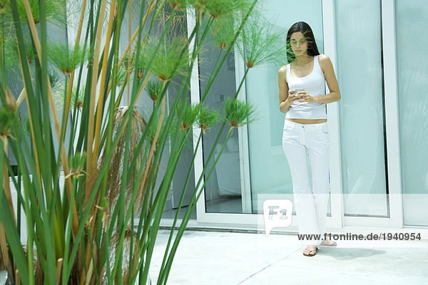 Woman standing by sliding glass door  holding cup  full length portrait