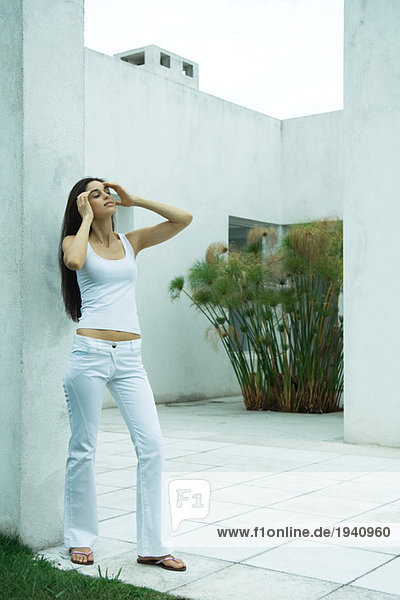 Woman standing  pushing hair back  full length portrait