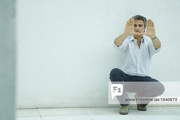 Der reife Mann kauert  macht mit den Händen einen Rahmen  schaut in die Kamera.