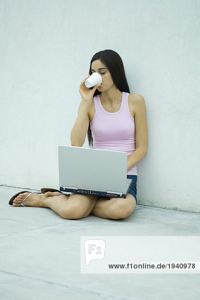 Woman sitting on ground  using laptop and drinking from disposable cup  full length