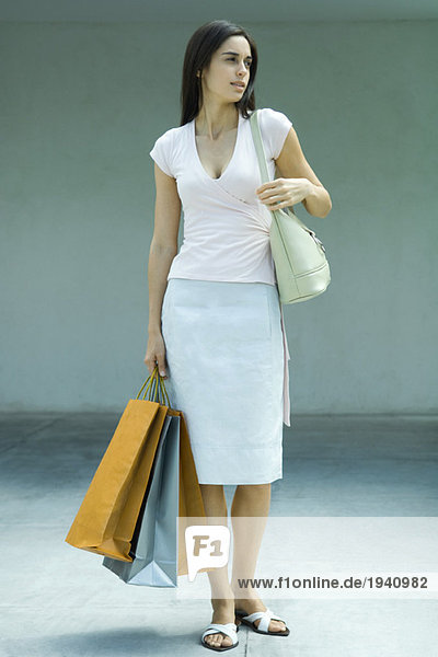 Woman holding shopping bags  full length portrait