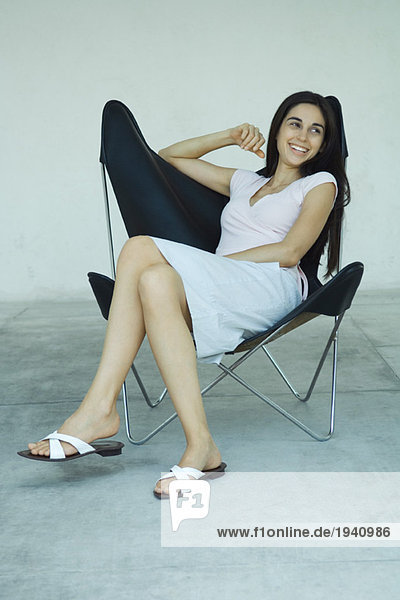 Young woman sitting in chair  leaning back  smiling  full length portrait