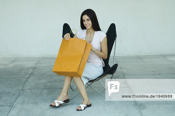 Young woman sitting in chair  opening shopping bag  smiling  full length portrait