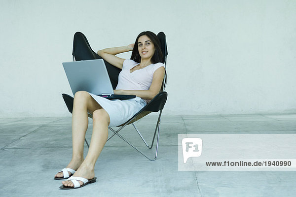 Young woman sitting back in chair  using laptop  full length portrait
