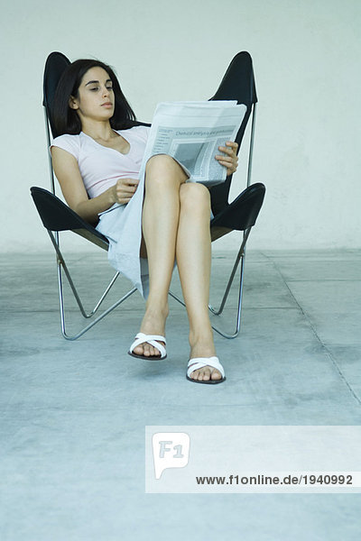 Young woman sitting in chair with legs crossed  reading newspaper  full length portrait