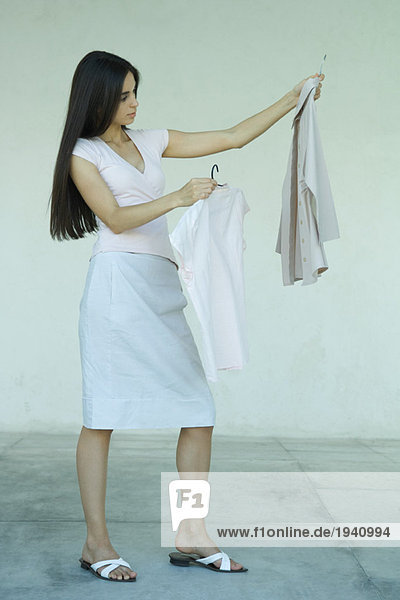 Woman standing  holding up two shirts on hangers  full length portrait