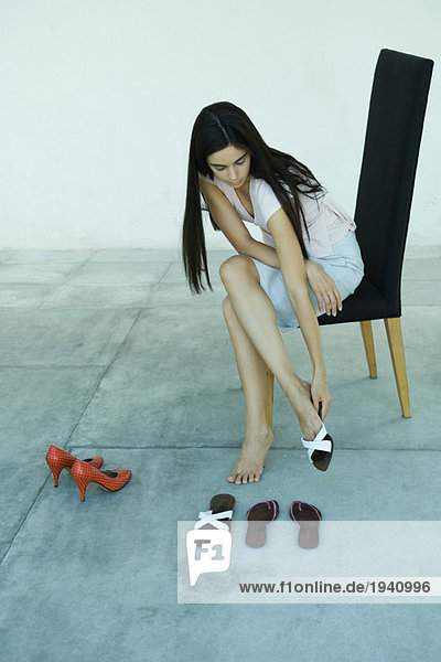 Young woman sitting in chair  trying on pair of shoes  full length portrait
