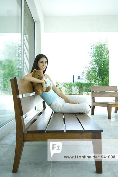 Young woman sitting on bench  holding teddy bear  full length portrait