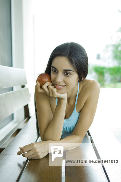 Young woman lying on bench  holding apple
