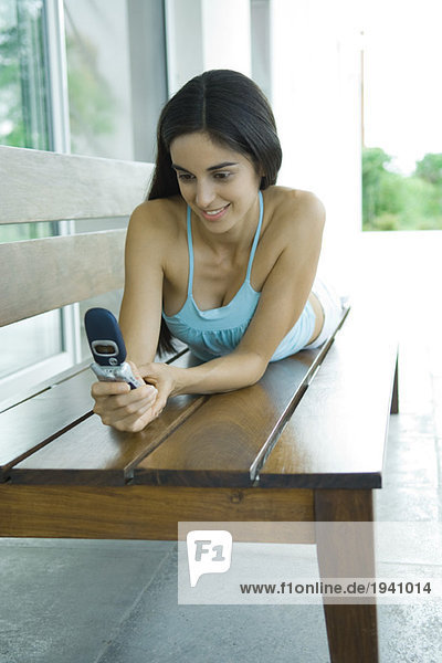 Young woman lying on bench  holding cell phone