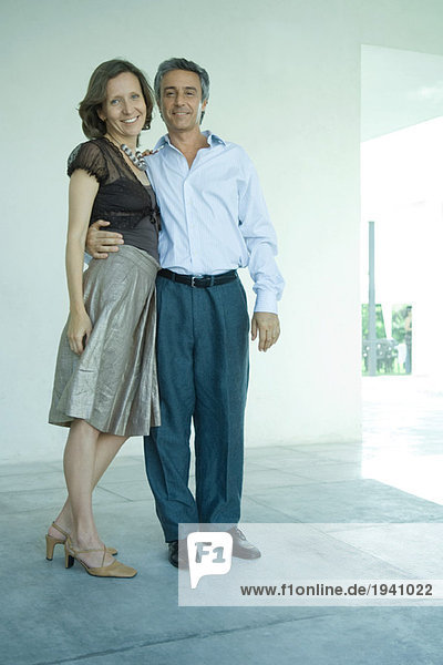 Mature couple standing together  man's arm around woman's waist  smilng at camera  full length portrait