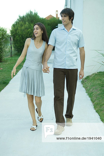 Young couple holding hands as they walk down sidewalk  looking out of frame