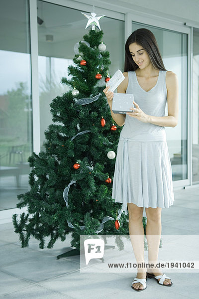 Young woman standing by Christmas tree  opening gift
