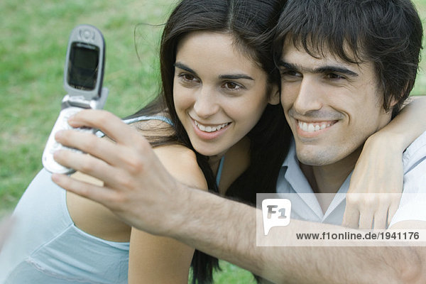 Young couple posing while man holds up cell phone to take photo