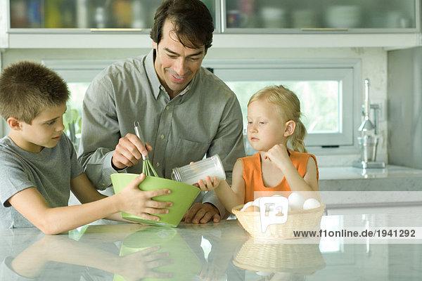 Vater kocht mit Sohn und Tochter