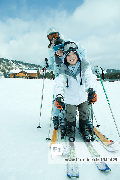 Young skiers on snow  smiling at camera  full length  portrait