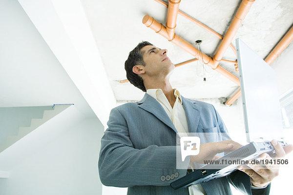 Gut gekleideter Mann mit Laptop  der das unfertige Interieur inspiziert.