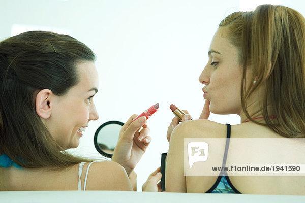 Zwei junge Freunde halten Lippenstift hoch  einer schaut in den Handspiegel  Rückansicht  Mund