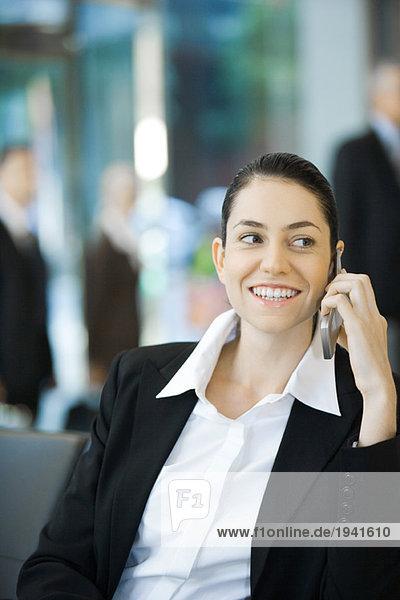 Junge Geschäftsfrau mit dem Handy  lächelnd  tailliert
