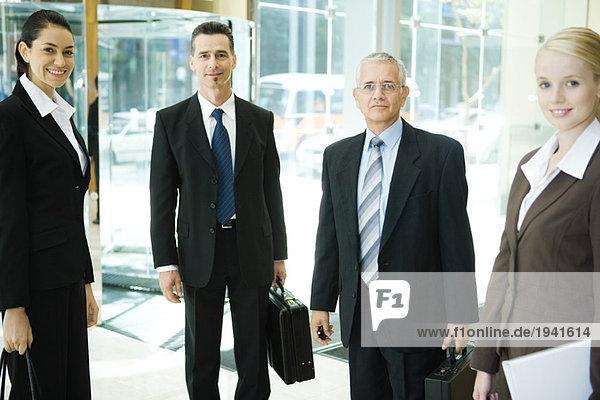 Geschäftspartner stehen in der Lobby und lächeln vor der Kamera.