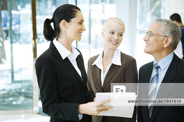 Geschäftsfreunde stehen  lächeln sich an  ein haltender Binder