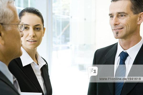 Drei Geschäftspartner beim Chatten  Ausschnittansicht