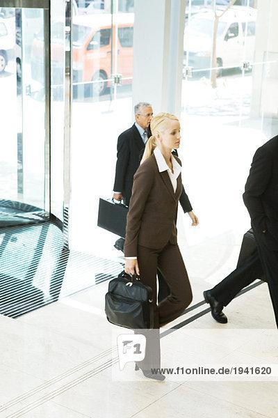 Junge Geschäftsfrau betritt Lobby  trägt Aktentasche  Mann im Hintergrund