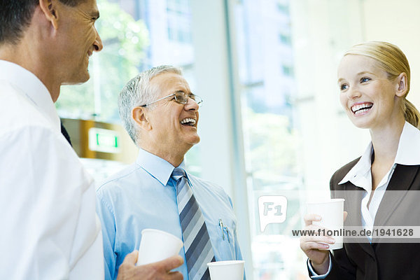 Business associates laughing together  holding hot beverages