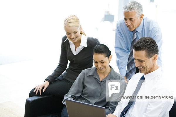 Vier Geschäftspartner  die gemeinsam auf den Laptop schauen  lächelnd