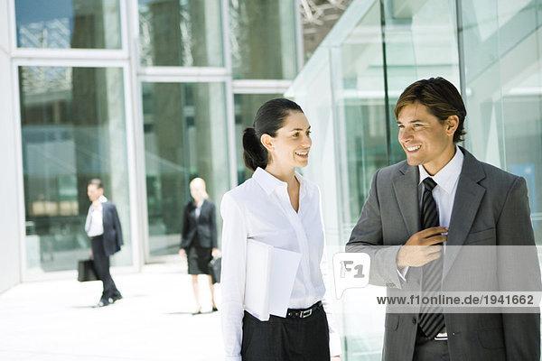 Junge Geschäftsfreunde stehen zusammen  plaudern  lächeln