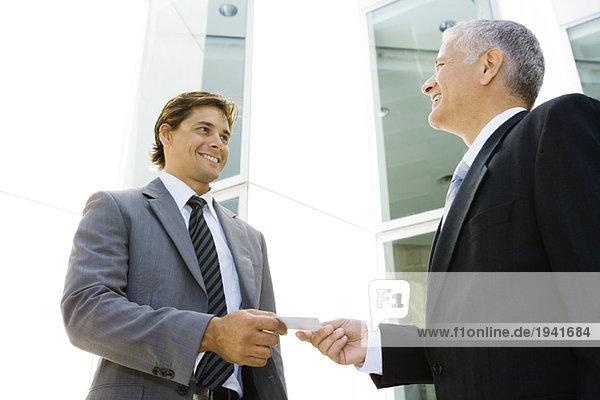 Zwei Geschäftsleute tauschen ihre Visitenkarte aus  lächeln sich an  Blickwinkel niedrig