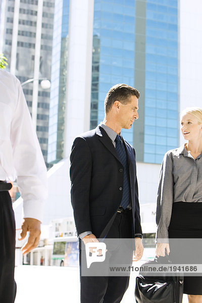 Two business associates standing on sidewalk  looking at each other  discussing
