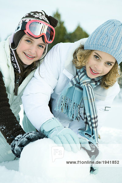 Two teenage girls crouching in snow  making snowball together  both smiling at camera