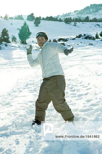 Junger Mann wirft Schneeball  lächelt in die Kamera  volle Länge