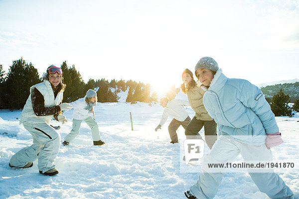 Young friends running in snow  dressed in winter clothing