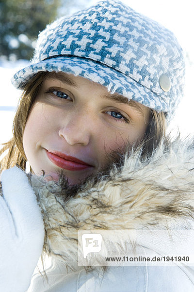 Teenage girl wearing parka and cap  close-up portrait