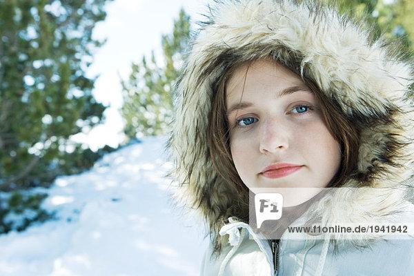 Teenage girl wearing parka in snowy landscape  portrait