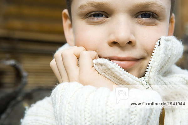 Boy holding collar of wool sweater over face  smiling at camera  close-up  portrait