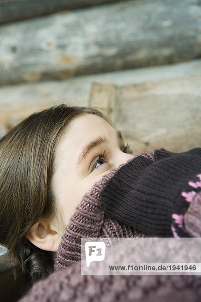 Teenage girl holding edge of sweater neck over face  looking up  close-up