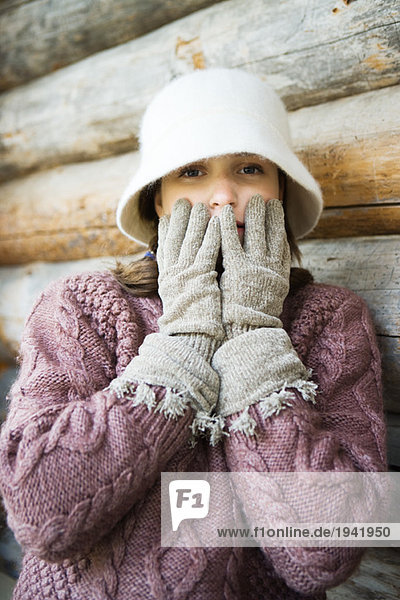 Teenage girl holding gloved hands over mouth