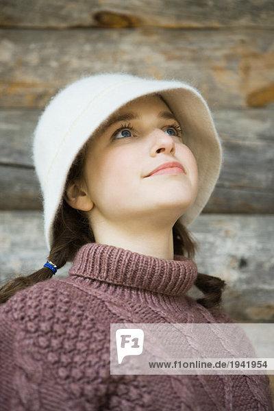 Teenage girl wearing hat and turtleneck  looking up  portrait