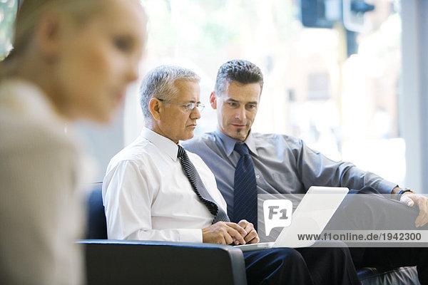 Zwei Geschäftspartner  die gemeinsam in der Lobby auf den Laptop schauen