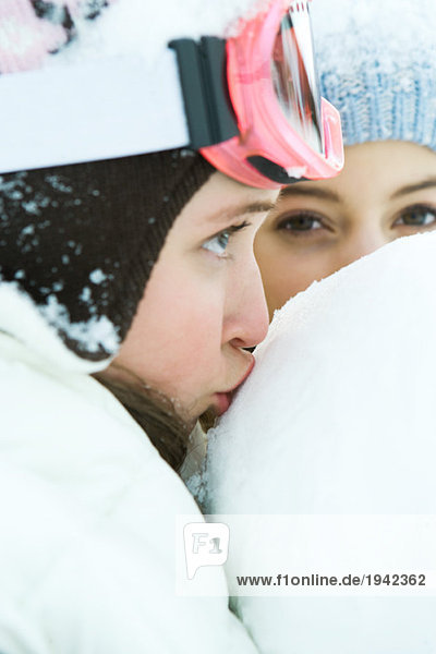 Teenage girl kissing snowball  close-up  friend in background