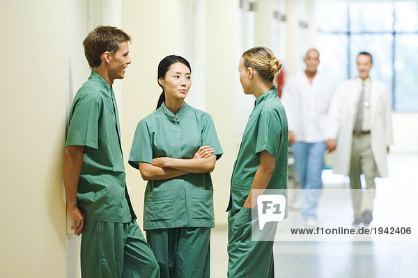 Three young medical colleagues standing in hallway  having discussion