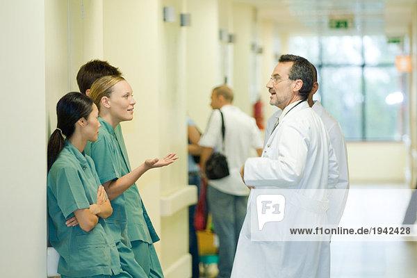 Junges Krankenhauspersonal im Gespräch mit einem reifen Arzt  Seitenansicht