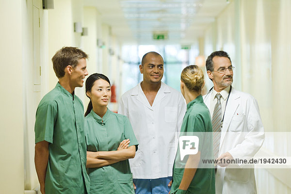 Medical staff standing in hallway  chatting  looking away